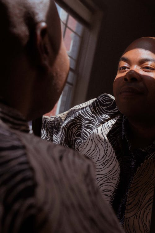Crop content stylish black man looking in mirror