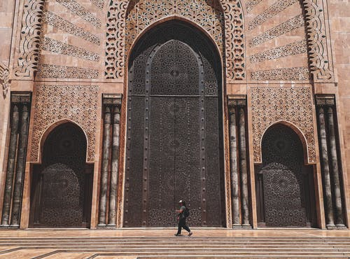 Side view unrecognizable person walking on piled steps of ornamental impressive mosque entrance in oriental style