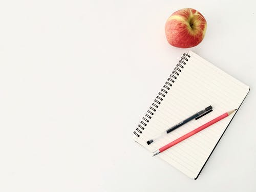 Top view composition of pen and pencil placed on spiral opened notebook with blank sheets near red ripe apple on white desk