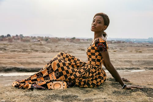 Serene black woman in stylish maxi dress on dry lawn