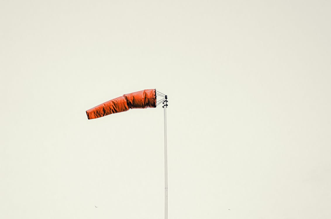 Red windsock on pole against gray sky