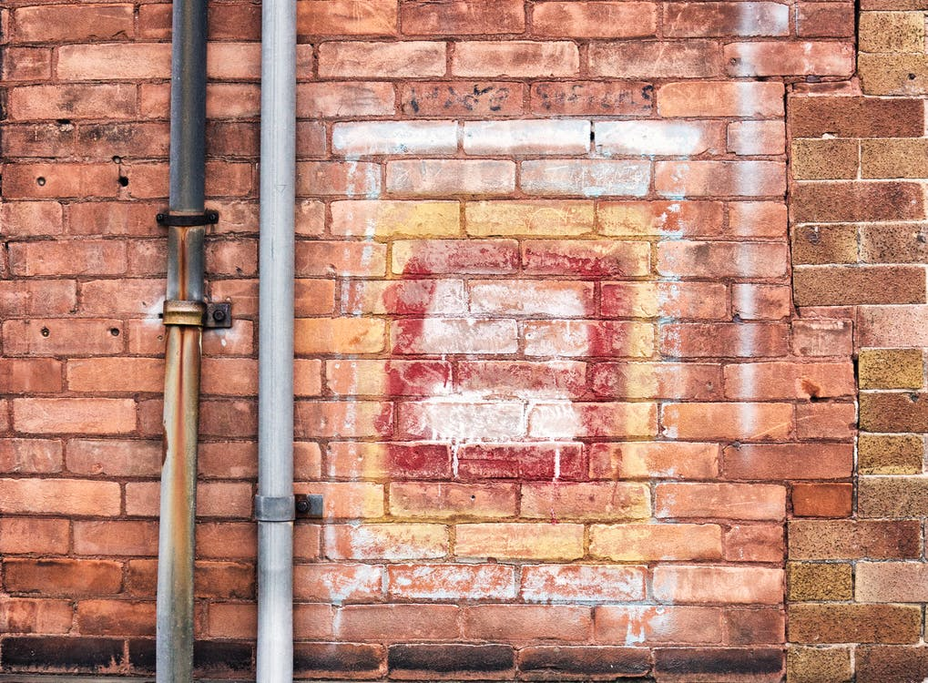 Gray Pipe on Brick Wall