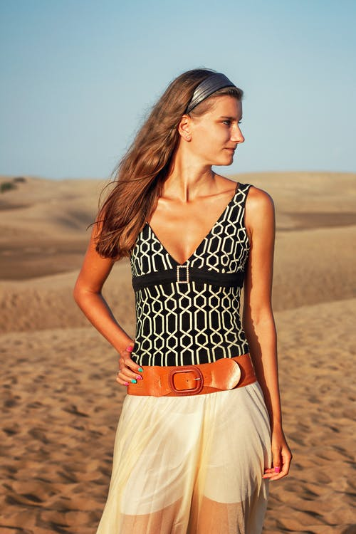 Woman in Black and White Polka Dot Tank Top and White Skirt Standing on Brown Sand