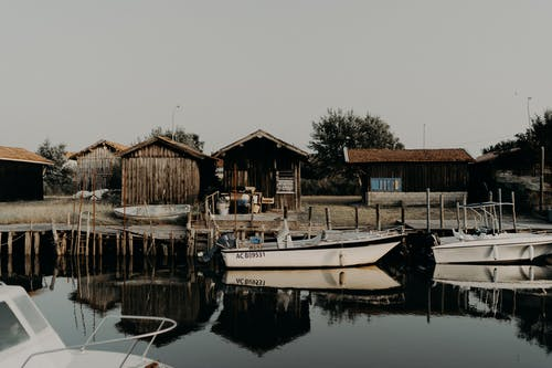 Shabby houses on lake shore with boats