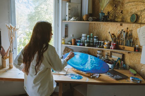A Woman Painting on a Surfboard Shaped Wood