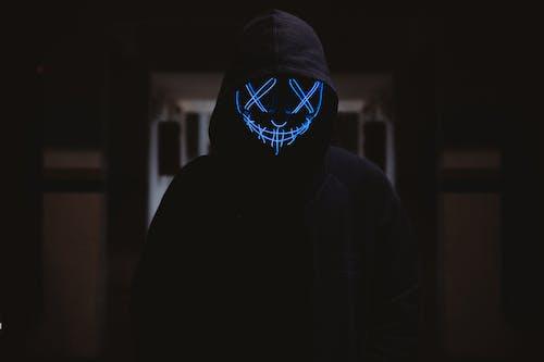 Photos gratuites de fond sombre, lumière bleue, masque de gars fawkes