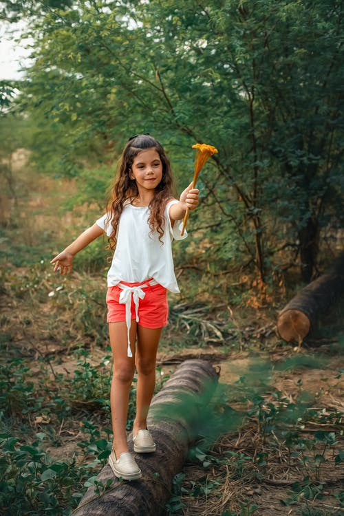 Girl in White Shirt and Red Shorts Holding Orange and Black Stick