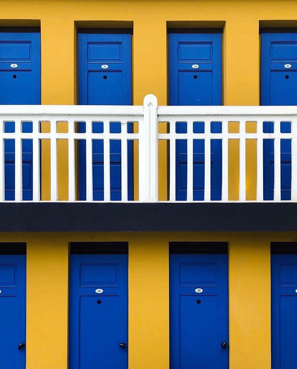 Exterior of old fashioned motel with yellow walls and bright blue doors in row