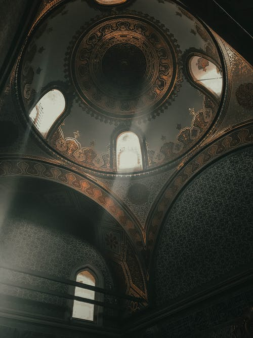 From below dome inside of ancient Topkapi Palace located in Istanbul decorated with arches and golden ornaments