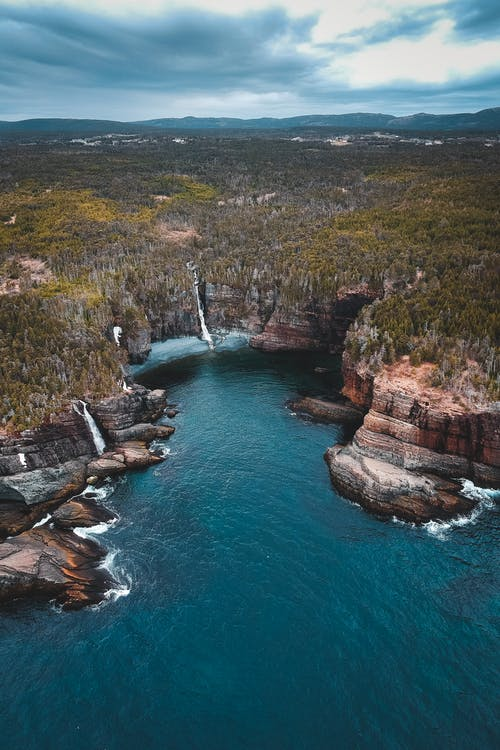 Amazing drone view of lush forest located on rocky cliff with waterfall flowing into turquoise sea against overcast sky