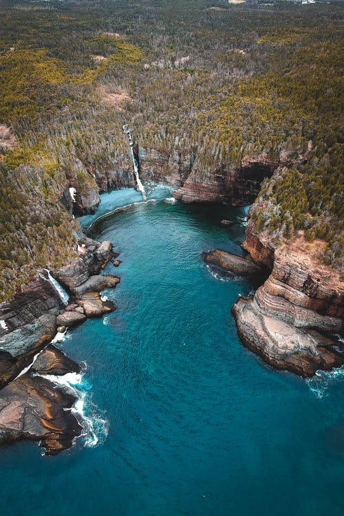 Turquoise sea coast surrounded by rocky cliff covered with lush trees