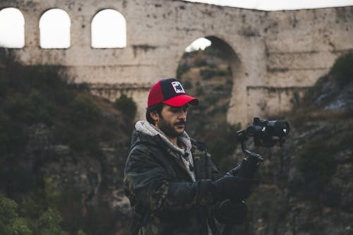 Man in Black and Gray Camouflage Jacket Holding Black Dslr Camera