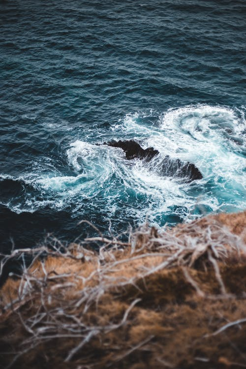 Swirling sea waves crashing on rocky cliffs