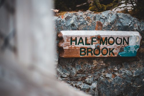 Shabby lumber board with inscription Half Moon Brook placed on rocky stone in nature park