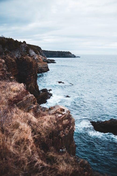 Scenery of rocky seashore washed by foamy seawater