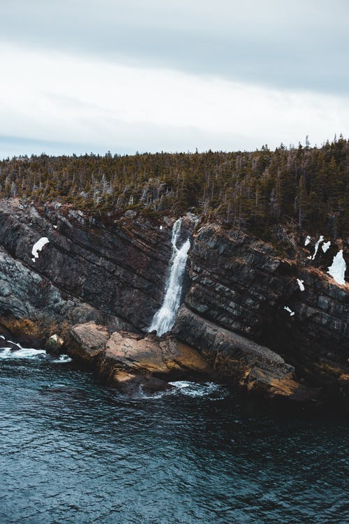 Rapid waterfall flowing through rough cliff covered with coniferous forest near calm rippling sea on autumn day