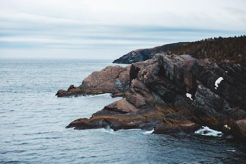 Calm rippling sea washing rough mountainous coast