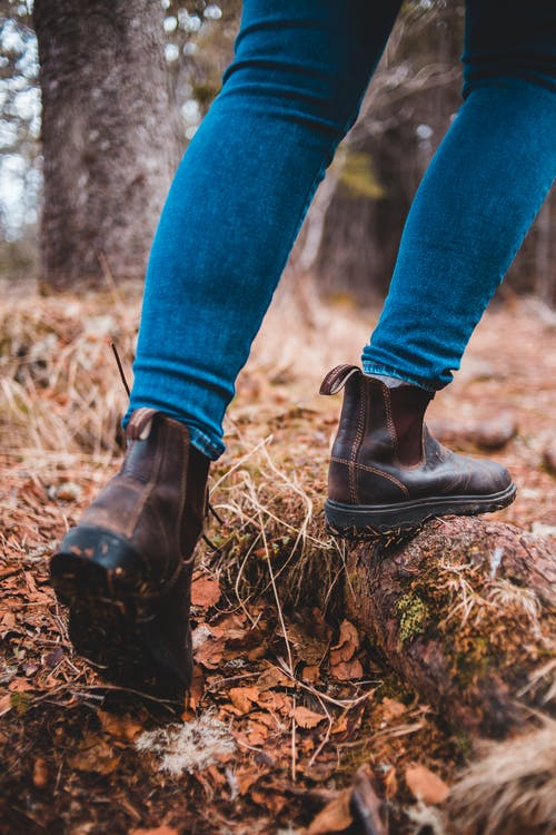 Person in Blue Denim Jeans and Brown Leather Boots