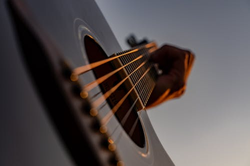Crop unrecognizable male musician placing fingers on modern acoustic guitar frets while performing in studio