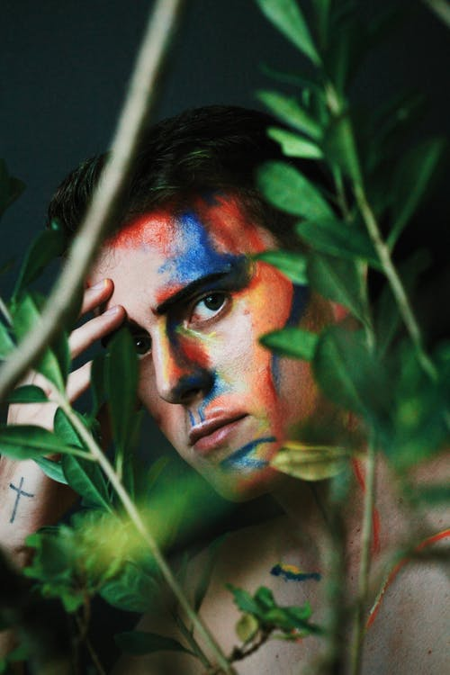 Concentrated young male model with body art on face standing in green plants branches and touching forehead during photo session in studio