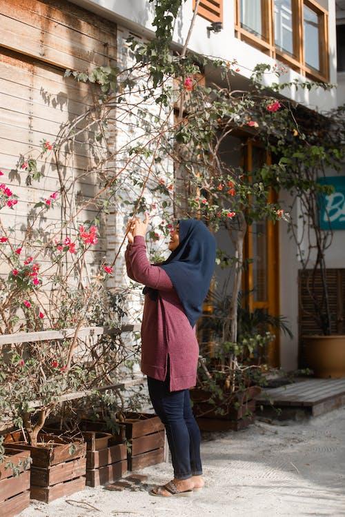 Woman in head scarf picking flowers