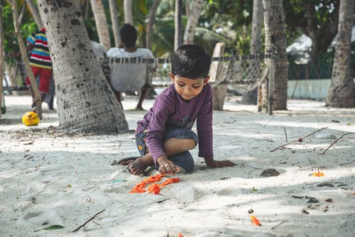 Boy in Purple Long Sleeve Shirt Sitting on Sand