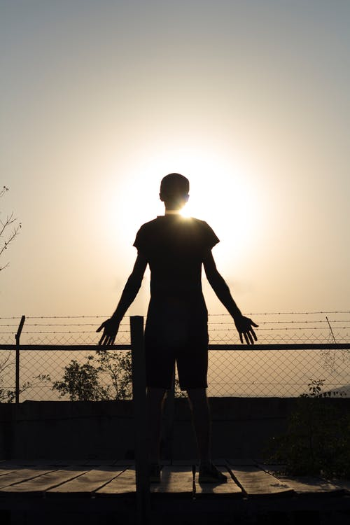 Silhouette of Man Standing Near Fence