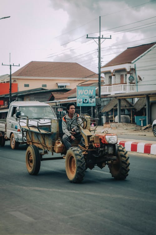 Ethnic man driving all terrain vehicle on roadway