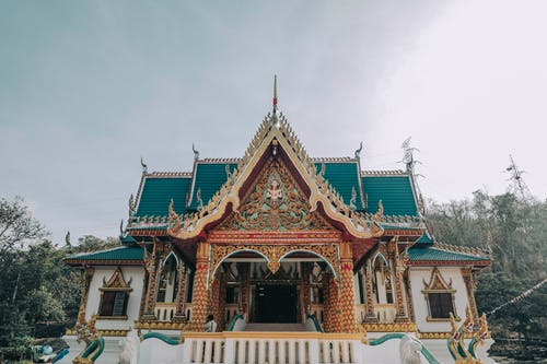 Aged Asian temple with decorative roof under sky