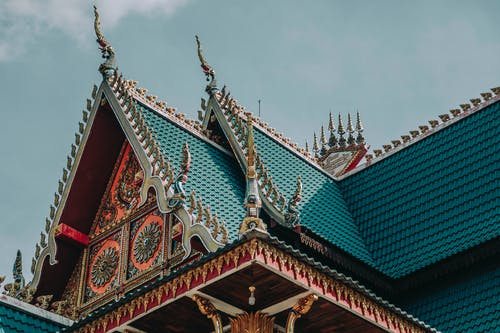 From below of bright ornamental roof with pointed peaks of aged Asian church under cloudy sky