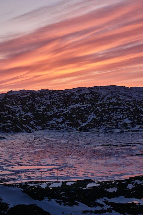 Snowy ridge near frozen pond under bright sky at sundown