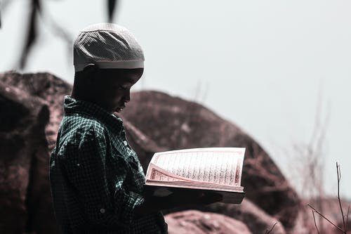 Photo Of Boy Holding Religious Book