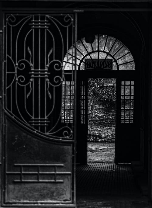 Black and white of aged decorated metal door of house with shabby wall in darkness