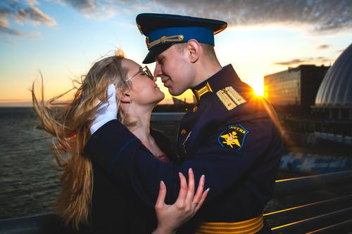 Smiling man in navy uniform embracing girlfriend near ocean