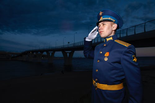 Military male patriot in uniform near bridge at night