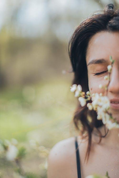 Crop woman smelling blooming flowers in park