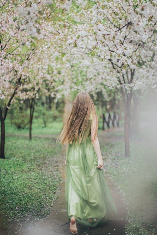 Woman in Green Dress Walking Near White Petaled Flowers