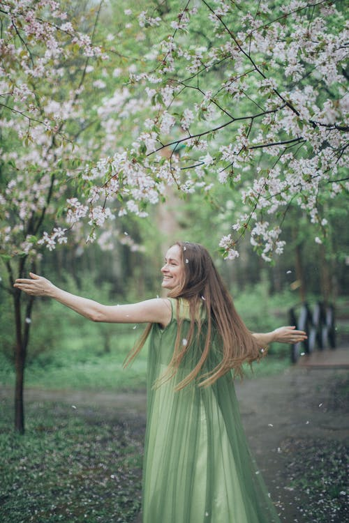Woman in Green Dress Standing Under White Petaled Flowers