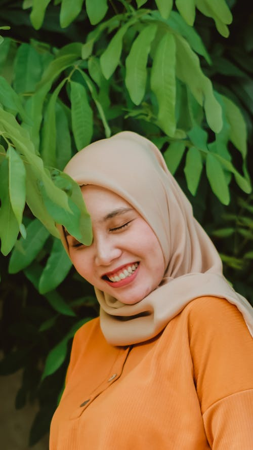 Photo of Woman Wearing Hijab Smiling While Standing Near Green Leaves