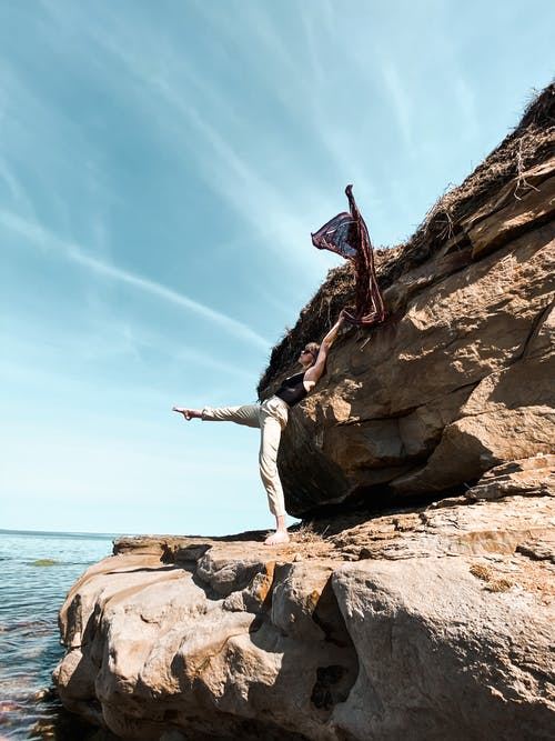 Side view of anonymous barefoot traveler reaching leg while leaning on rough mount and raising shawl near ocean under cloudy sky during summer vacation