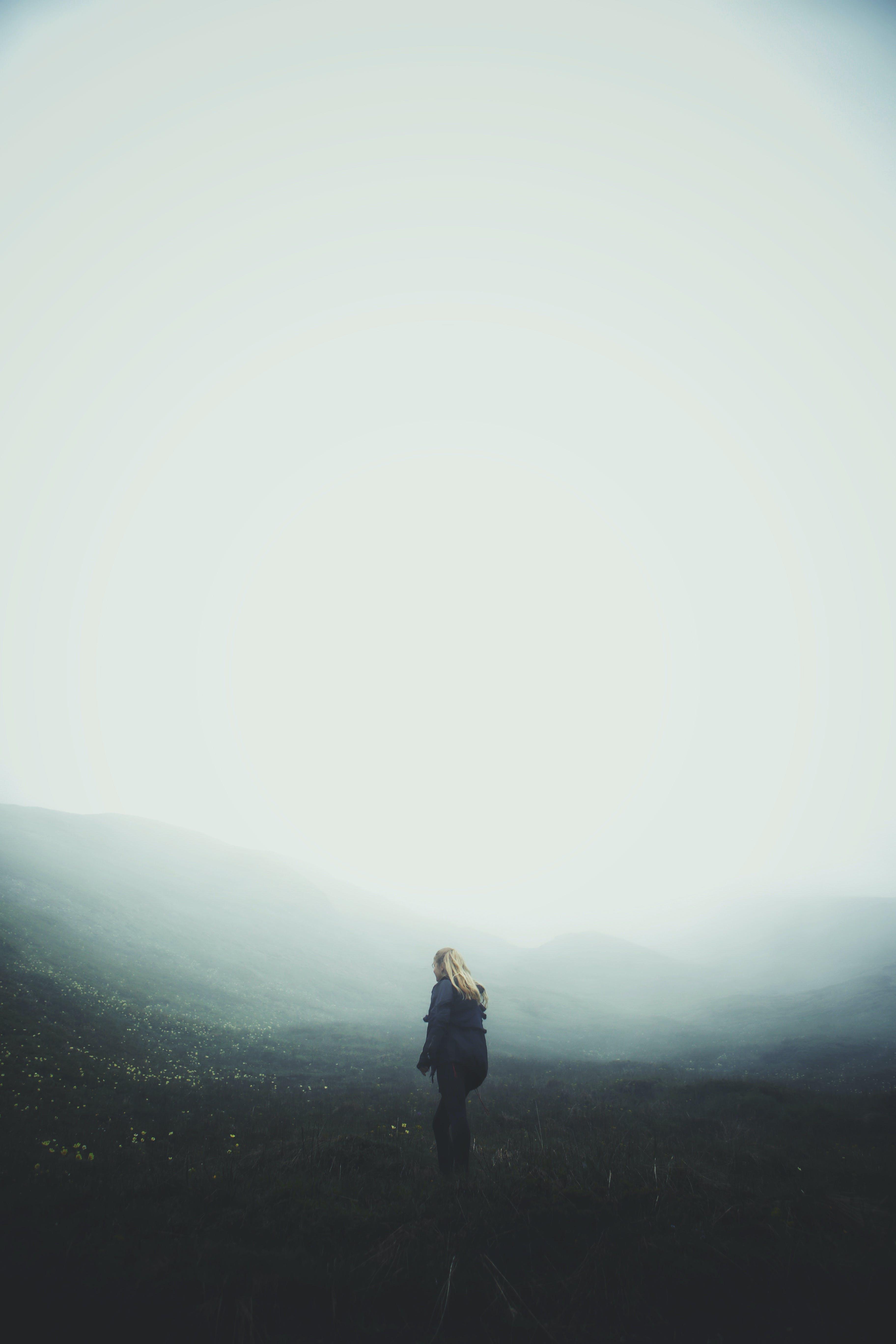 Woman Wearing Blue Jacket Standing on Grass Fiels'