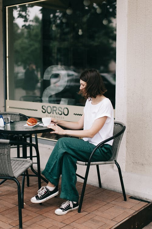 Woman in White T-shirt and Green Pants Sitting on Black Metal Chair