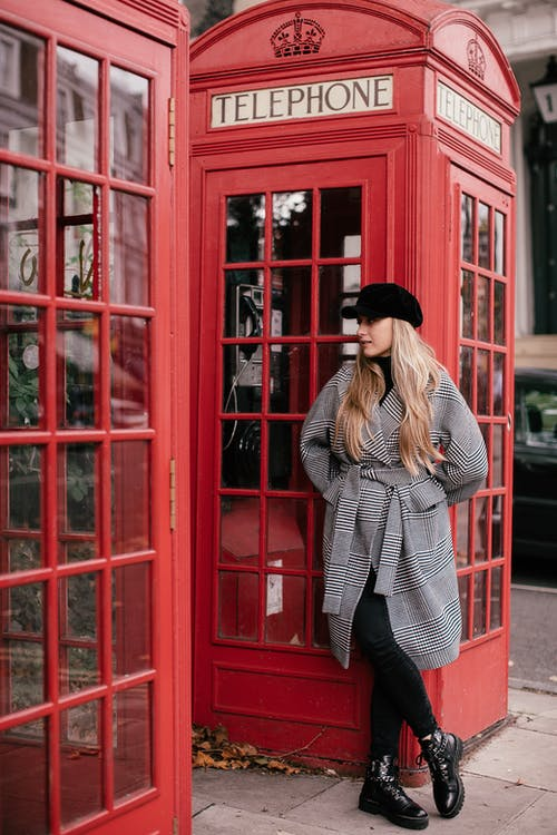 Woman in Black and White Checkered Long Sleeve Shirt and Black Hat Standing Beside Red Telephone