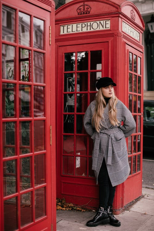 Woman in Red and White Plaid Coat Standing Beside Red Telephone Booth
