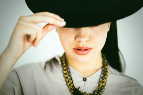 Crop stylish woman in hat and necklace on white background
