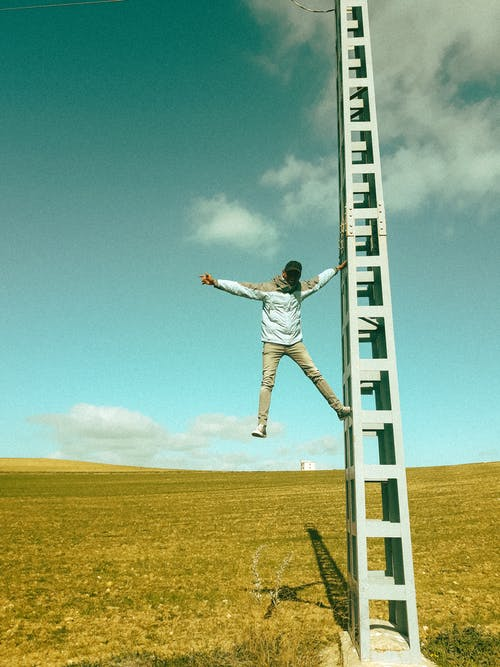 Unrecognizable man hanging on tower in field