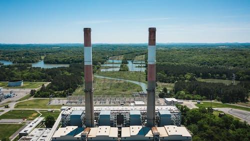 Industrial chimneys on power plant platform under sky