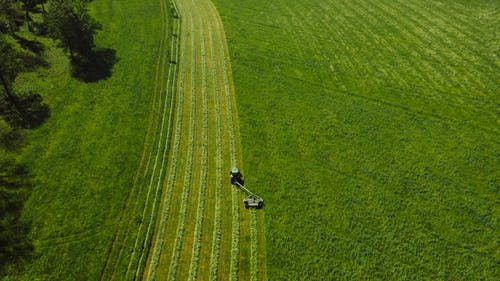 Aerial View of Tractor Landscape Rake on Green Grass Field
