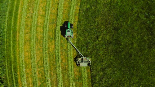 Top View Photo of Tractor Landscape Rake on Grass Field