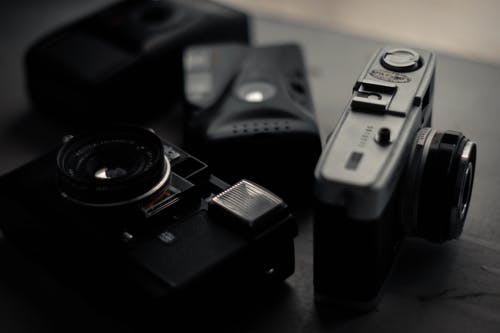 Different aged photo cameras on desktop in apartment